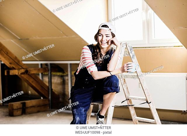 Young woman on construction site of her new home, holding