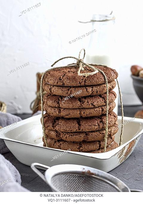 stack of chocolate chip cookies in a round white bowl, iron, behind a bottle of milk