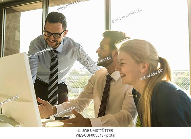 Three happy young business people in conference room looking at monitor