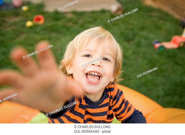 Young boy reaching towards camera