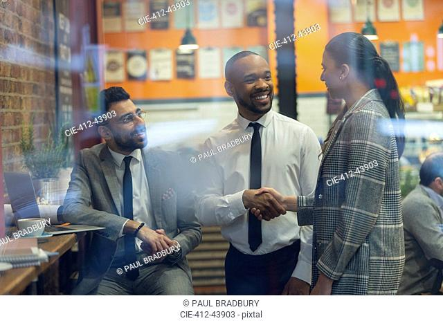 Smiling business people handshaking in cafe