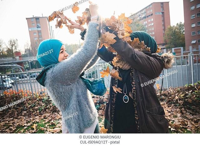Two young women in park play fighting with autumn leaves