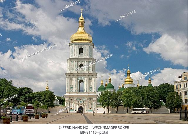 Ukraine Kiev view to Sophien place with big belltower and the shining golden domes of Sophien cathedral 1054 tourists visitors road with cars historical...