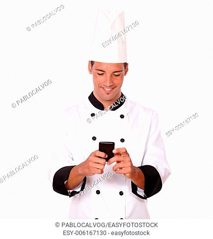 Portrait of professional young chef on white uniform texting a message with his mobile while smiling and standing on isolated studio