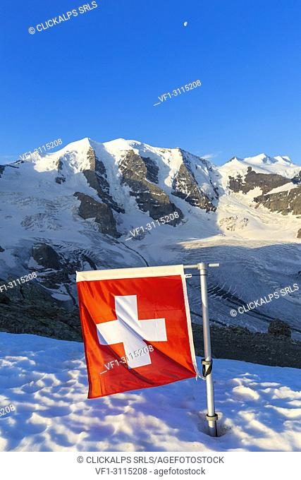 Switzerland flag with Palù Peaks and Vedret Pers Glacier in the background. Diavolezza Refuge, Bernina Pass, Engadin, Graubünden, Switzerland, Europe
