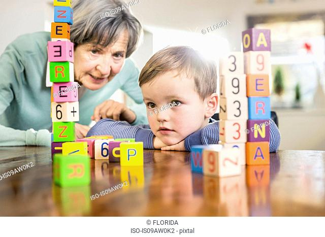 Boy and grandmother playing with alphabet bricks at kitchen table
