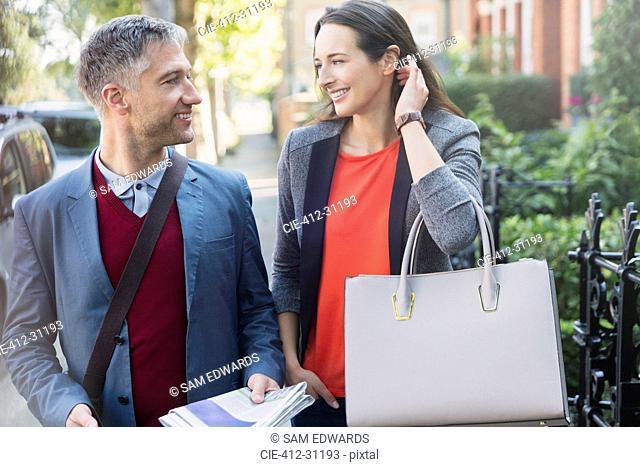 Business couple talking on morning sidewalk