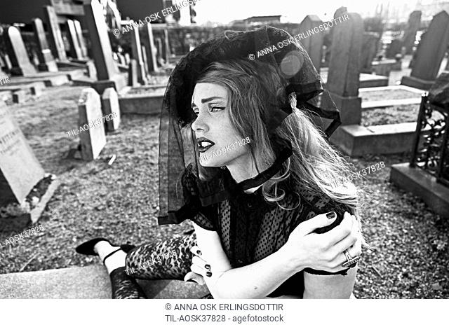 Lone female figure wearing black dress and veil sitting on grave