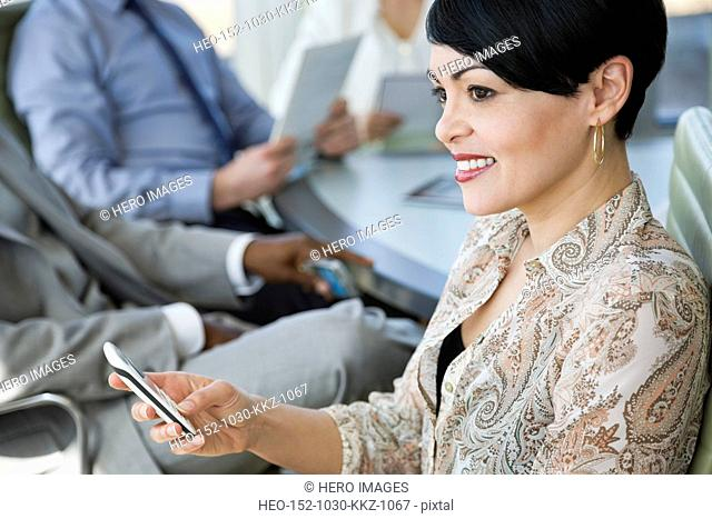 Businesswoman with smartphone in business meeting