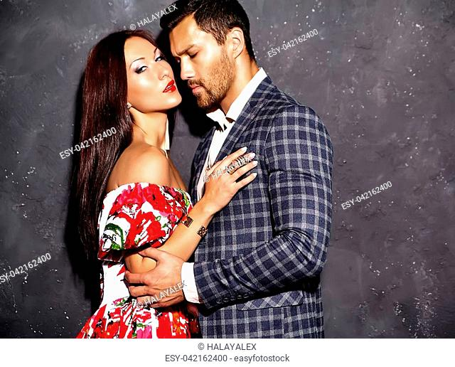 Fashion photo of handsome elegant man in suit with beautiful sexy woman posing near gray wall