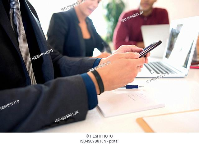 Cropped shot of businessman looking at smartphone during meeting