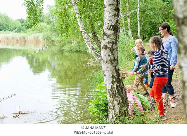 Germany, Children watching toy raft in water