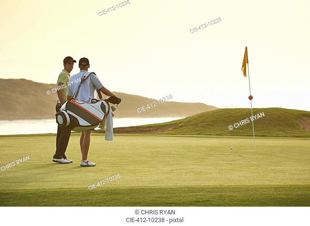 Men on golf course overlooking ocean