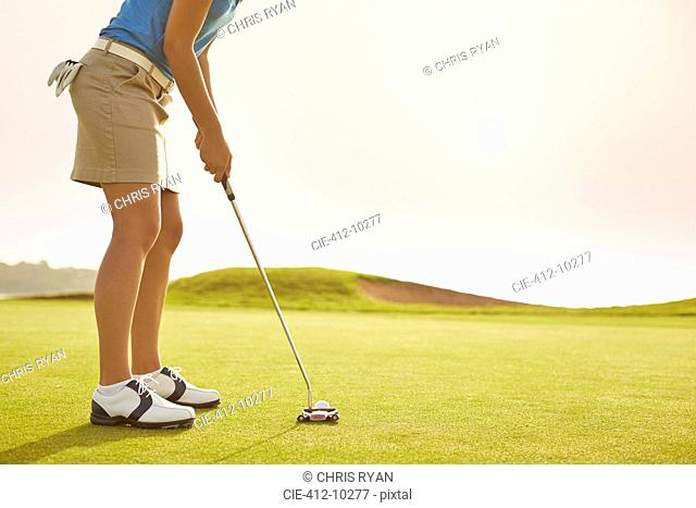 Woman putting on golf course