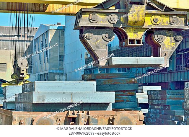 Crane loading sheet steel in plant