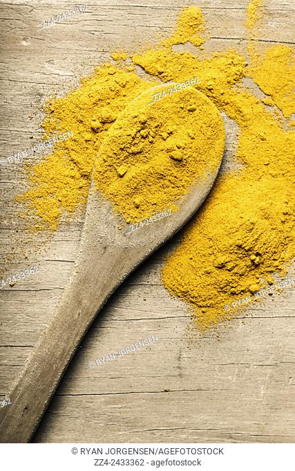 Closeup still life photo on yellow turmeric seasoning spice on wooden serving spoon. Indian curry ingredients
