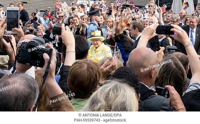 Britain's Queen Elizabeth II, accompanied by Berlin's Governing Mayor Michael Mueller (C-R), walks across Pariser Platz square in Berlin, Germany, 26 June 2015