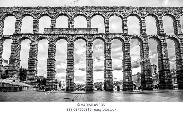 Famous ancient Roman aqueduct on Plaza del Azoguejo square in Segovia, Castilla y Leon, Spain - black and white version