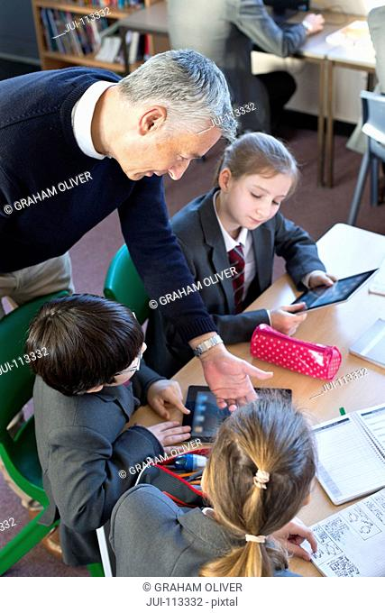 Teacher helping middle school students with digital tablet in classroom