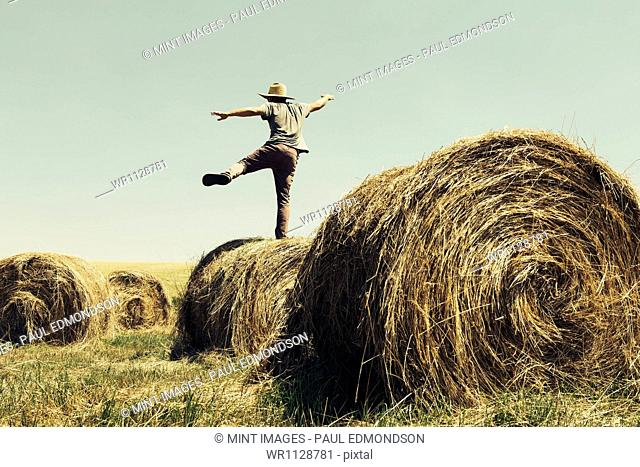 Back view of a man balancing on one leg on top of a hay bale