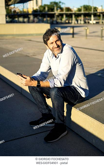 Smiling mature man sitting in the city holding cell phone