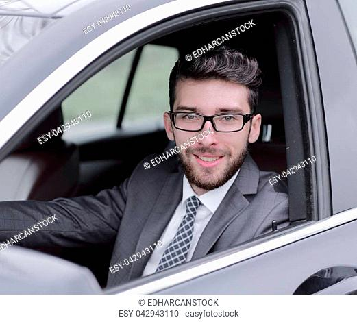 successful businessman in suit driving his luxurious car