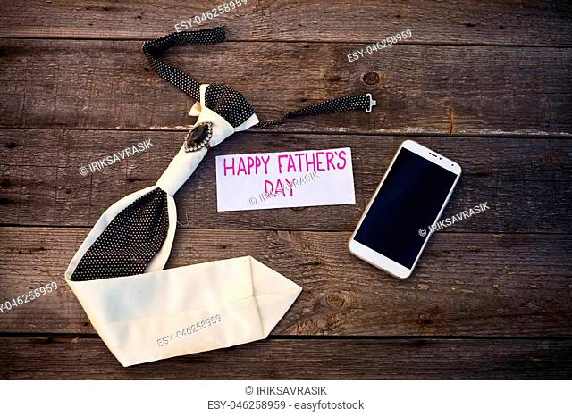 Happy Father's Day inscription with mobile phone and tie on wooden background. Greetings and presents