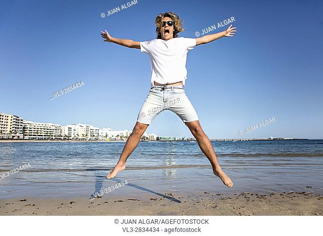 Young man jumping near the water