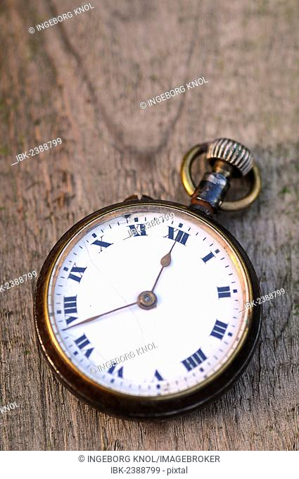Antique pocket watch lying on a wooden table