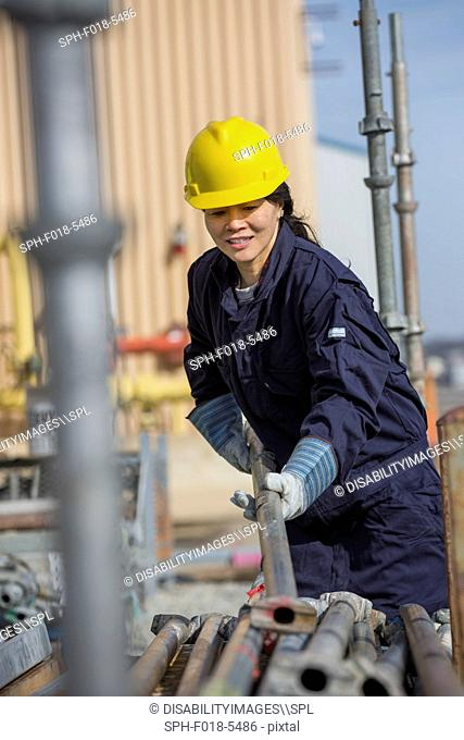 Female power engineer sorting through scaffolding at power plant