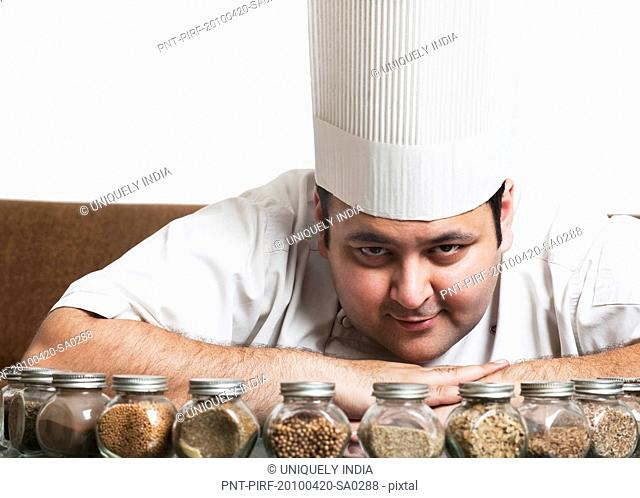Chef smiling with assorted spices on a table, Gurgaon, Haryana, India