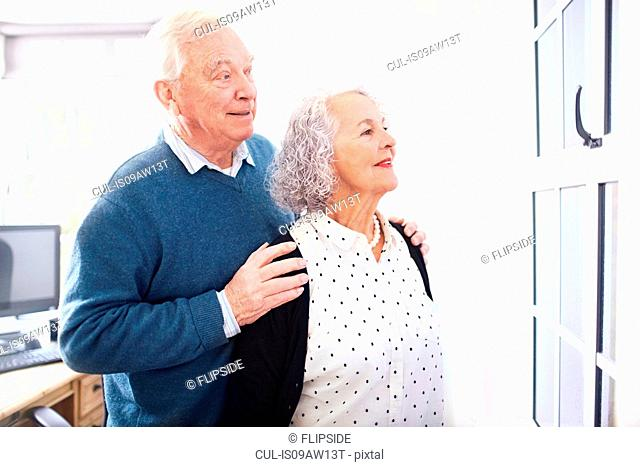 Senior couple in office looking out of window smiling