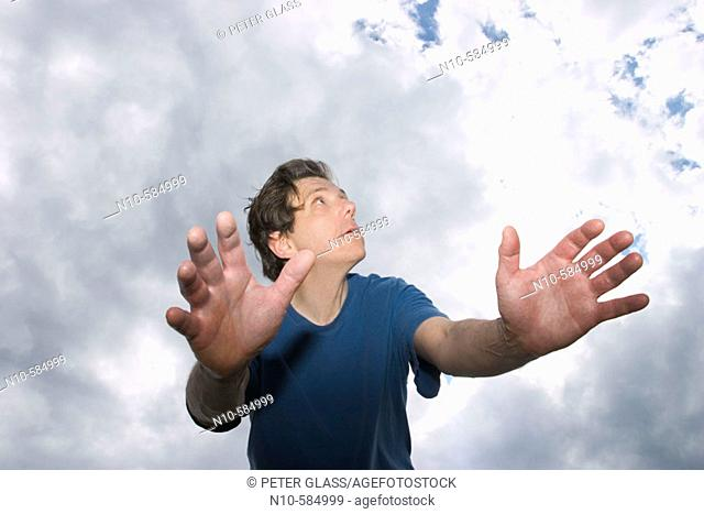 Middle-age man, with his arms outstretched, posing in front of a cloudy sky