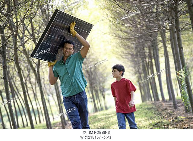 A man carrying a solar panel down an avenue of trees, accompanied by a child