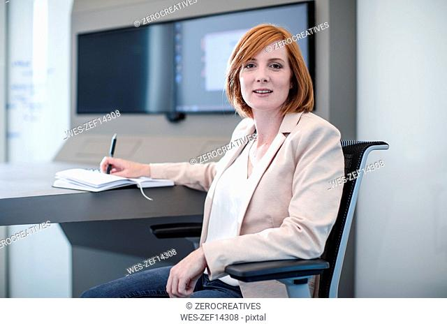 Woman sitting in office with her notebook