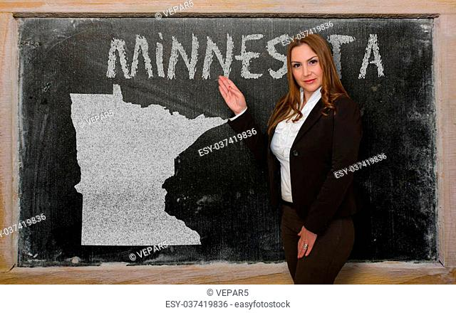 Successful, beautiful and confident young woman showing map of minnesota on blackboard for presentation, marketing research and tourist advertising