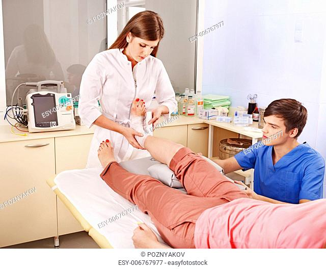 Doctor bandaging patient in hospital. First aid