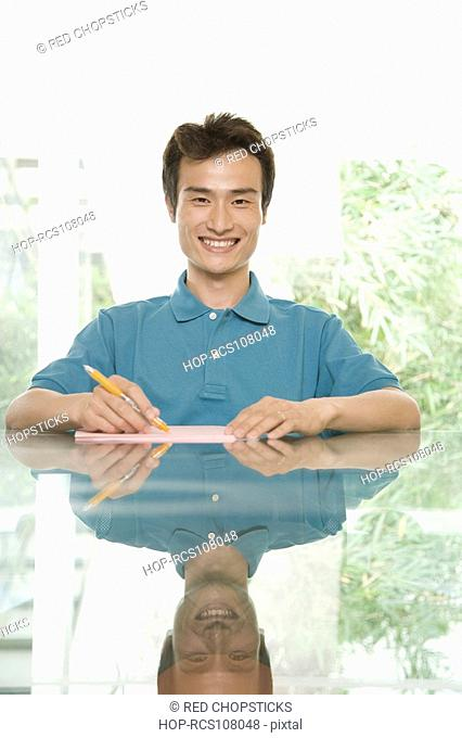 Portrait of a young man sitting at a conference table and smiling