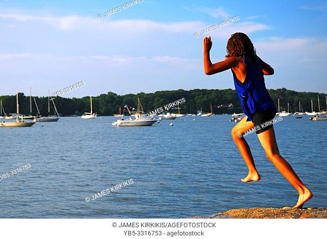 A young girl leaps into the sea