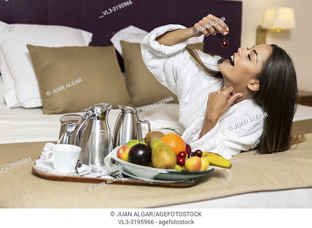 Young attractive woman lying on white and brown bedsheet and eating cherry with plate of different colorful fruits and coffee set put near