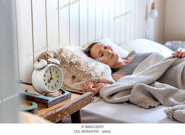 Woman in bed, alarm clock on bedside table