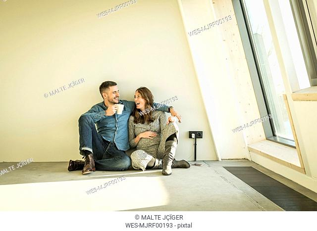 happy couple, expecting baby, sittig on floor of their new apartment