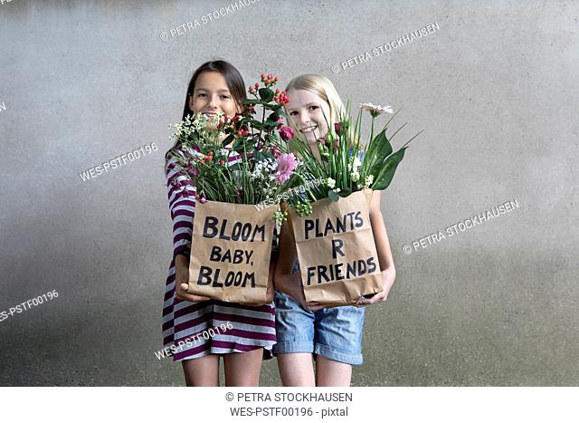Portrait of two smiling girls standing side by side offering paper bags with flowers