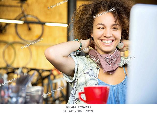Smiling woman at laptop in bike shop adjusting neck scarf