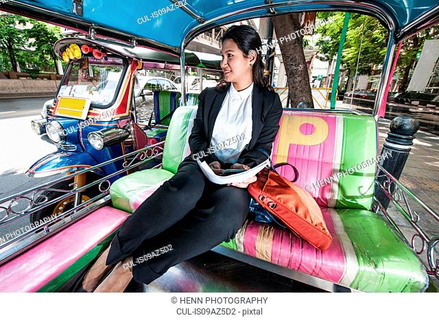 Businesswoman sitting in back of typical Thai tuk tuk taxi