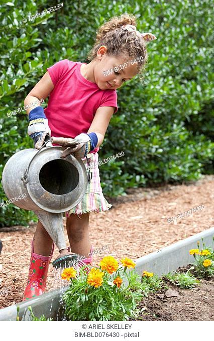 Mixed race girl watering flowers in garden
