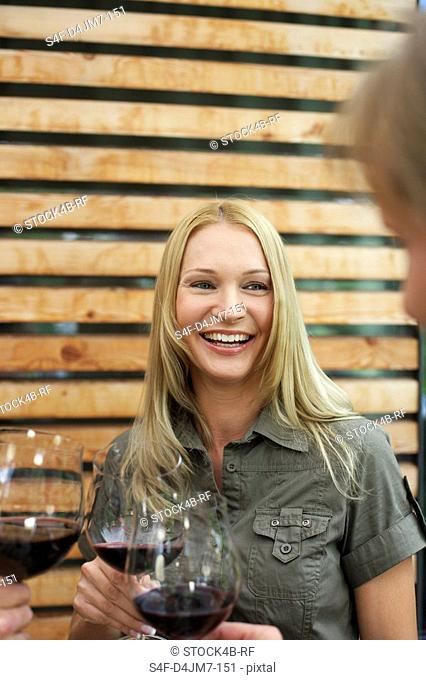 Laughing woman clinking glasses with red wine