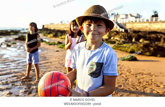 Portrait of boy with a ball on the beach at sunset