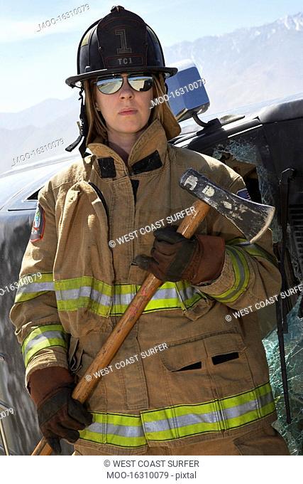 Portrait of female firefighter holding axe