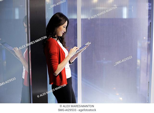 Young woman leaning against glass wall working on tablet